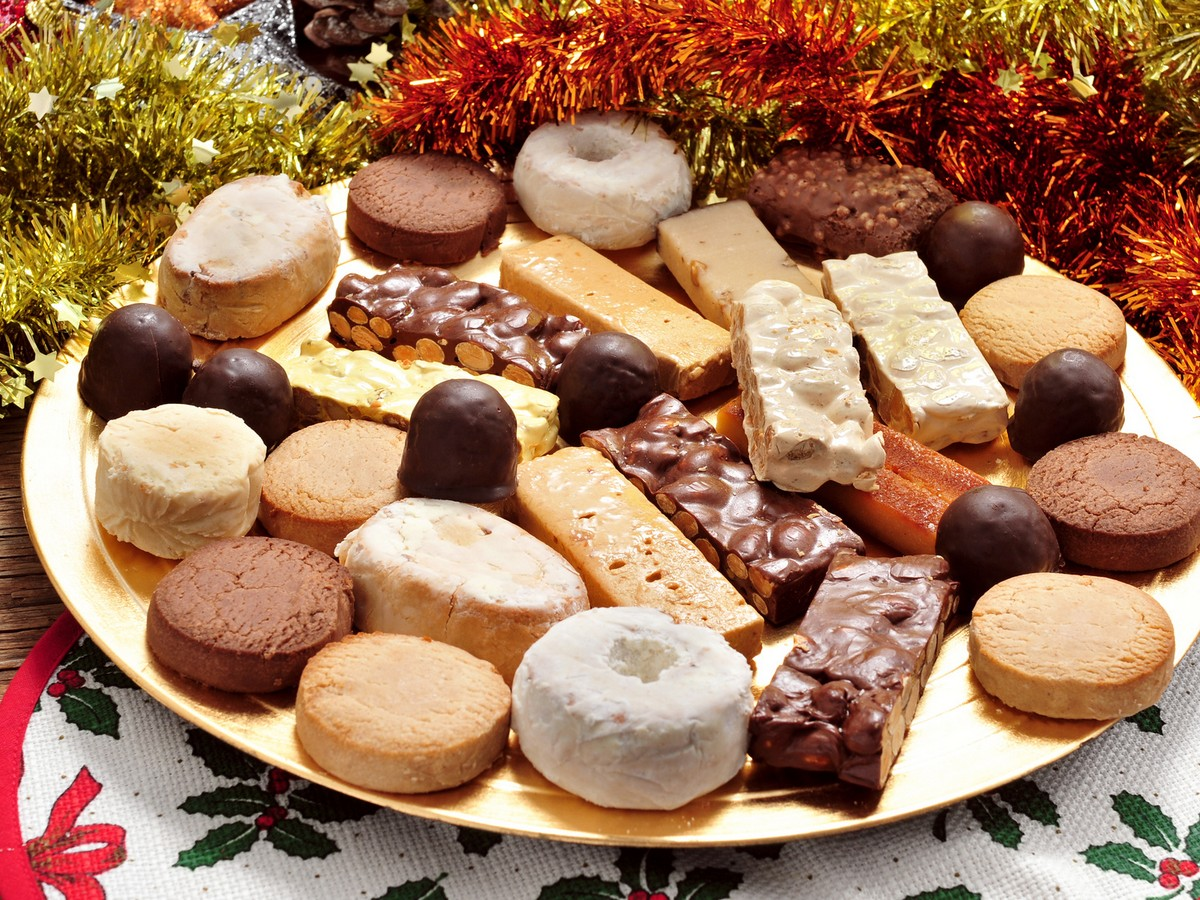 A Tray With Different Turron, Polvorones And Mantecados, Typical Christmas Confections In Spain, On An Ornamented Table